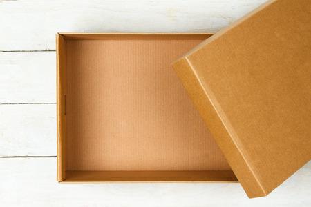 Photo pour Opened cardboard box on a wooden table - image libre de droit