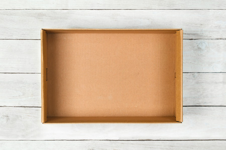 Photo pour Cardboard box on a white wooden  - image libre de droit