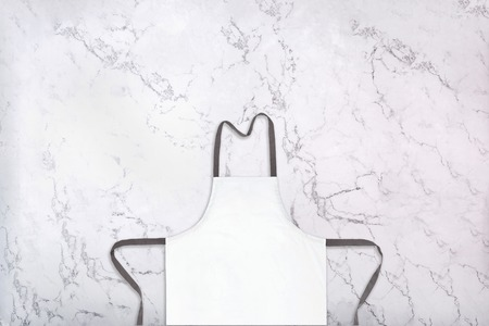 Photo pour Crop of white kitchen apron on natural marble texture. Blank apron on marble background. Top view - image libre de droit