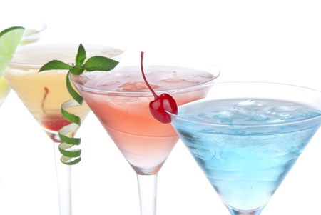 Summer Tropical Martini Cocktails with vodka, apple and peach liqueur, pineapple and cranberry juice, lime, lemon, blue curacao, maraschino cherry, and orchid isolated on a white background