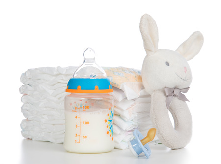Photo for New born child stack of diapers, nipple soother, beanbag bunny toy and baby feeding bottle with milk on a white background - Royalty Free Image
