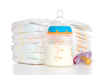 Photo pour New born child stack of diapers nipple soother and baby feeding bottle with milk on a white  - image libre de droit