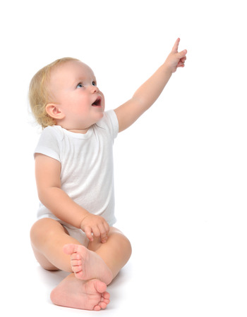 Photo pour Infant child baby toddler sitting raise hand up pointing finger at the corner isolated on a white background - image libre de droit