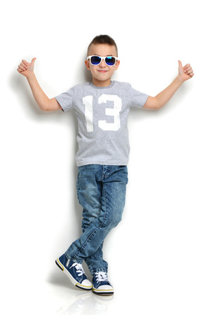 Photo pour Fashion beautiful little boy in sunglasses t-shirt jeans standing and giving thumbs up sign over white background - image libre de droit