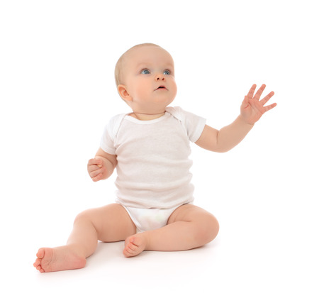 Photo pour Infant child baby toddler sitting raise hand up pointing fingers looking at the corner isolated on a white background - image libre de droit
