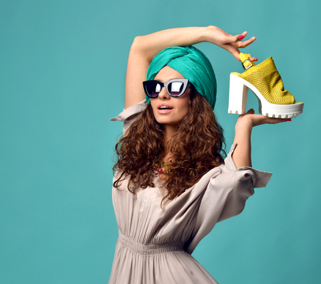 Photo pour High fashion look glamour beautiful curly hair American woman in modern cat eyes sunglasses with white yellow shoe and nails manicure on blue mint background - image libre de droit