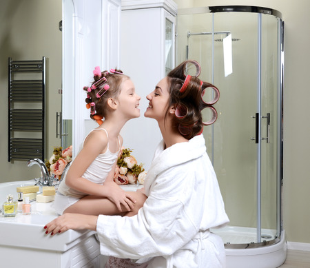 Photo pour Young mother and daughter in curlers in a bath room happy smiling family skin care concept in bathroom - image libre de droit