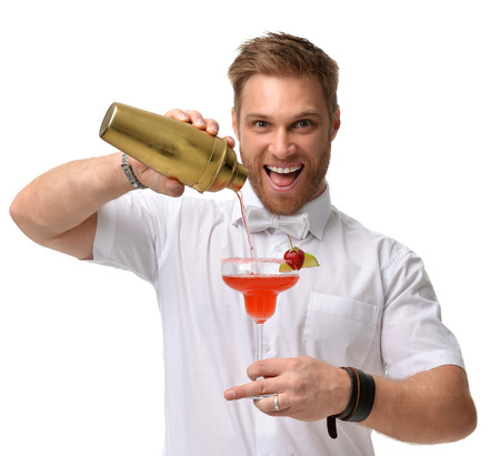 Photo for Bartender men is preparing red margarita cocktail with strawberry and lime. Hold big glass and pours alcohol from a gold shaker isolated on a white background - Royalty Free Image