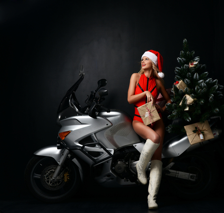 Foto de Portrait of sexy blonde woman in Christmas Santa costume sitting on motorcycle looking at the corner. Holidays New Year 2018 on dark background - Imagen libre de derechos