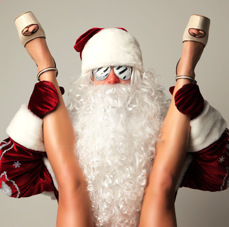 Photo for New year 2018 christmas concept. Bad santa claus in snow flakes sunglasses holding young sexy woman  long legs and high hills - Royalty Free Image