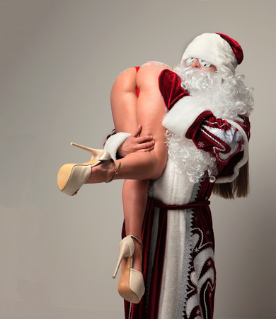 Foto de Bad santa claus in snow flakes sunglasses abduct young sexy naked ass woman with long legs and high hills. New year 2018 christmas concept - Imagen libre de derechos