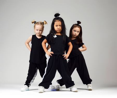 Foto de Group of three young girl kids hip hop dancers on gray background - Imagen libre de derechos