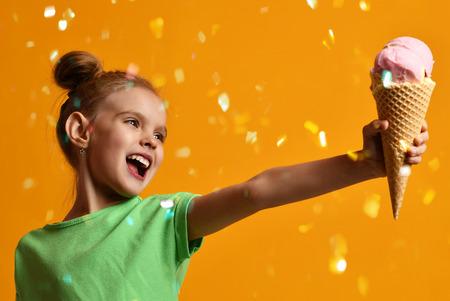 Foto de Pretty baby girl kid give away vanilla ice cream in waffles cone laughing and smiling on yellow background - Imagen libre de derechos