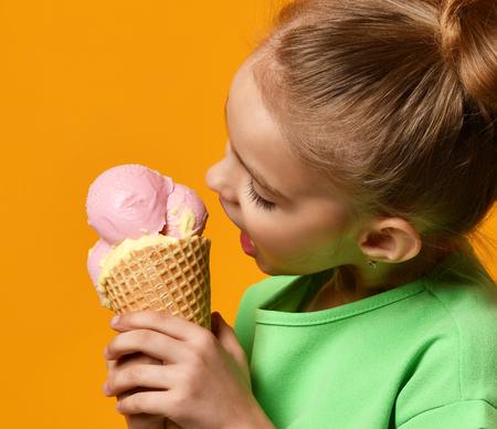 Foto de Pretty baby girl kid eating licking banana and strawberry ice cream in waffles cone on yellow background - Imagen libre de derechos