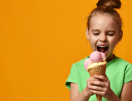 Photo for Pretty baby girl kid eating licking banana and strawberry ice cream in waffles cone on yellow background with free text copy space - Royalty Free Image