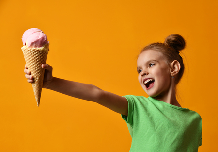Foto de Pretty baby girl kid hold strawberry ice cream in waffles cone on yellow background screaming laughing with free text copy space - Imagen libre de derechos