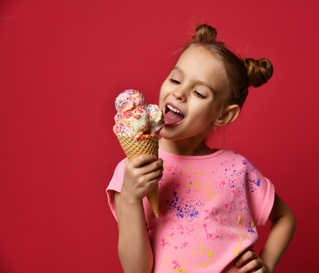Foto de Pretty baby girl kid eating licking big ice cream in waffles cone with raspberry happy laughing on red background - Imagen libre de derechos