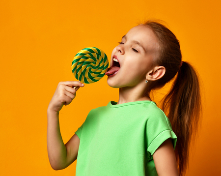 Foto de Happy young little child girl kid bite sweet lollypop candy on yellow background - Imagen libre de derechos