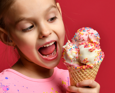 Photo pour Pretty baby girl kid eating licking big ice cream in waffles cone with raspberry happy laughing on red background - image libre de droit
