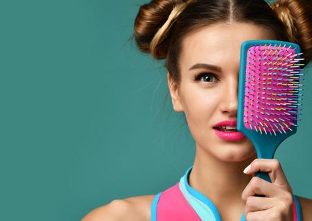 Foto de Closeup portrait of happy fashion brunette woman close eyes with colorful pink blue big hair comb brush on modern mint background - Imagen libre de derechos