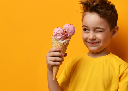 Photo pour Baby boy kid eating strawberry ice cream in waffles cone and winking on yellow background with free text copy space - image libre de droit