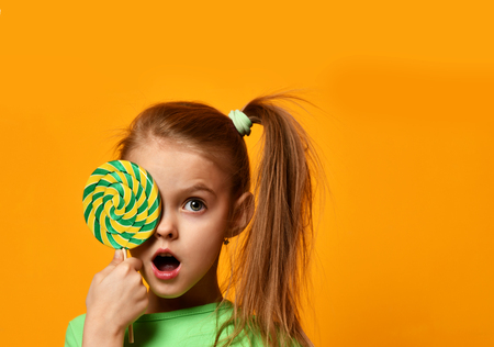 Foto de Happy young little child girl kid bite sweet lollypop candy on yellow background - Imagen libre de derechos