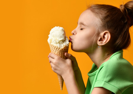 Foto de Pretty baby girl kid kiss vanilla ice cream in waffles cone on yellow background and show thumbs up sign with free text copy space - Imagen libre de derechos