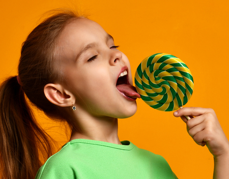 Photo pour Happy young little child girl kid bite sweet lollypop candy on yellow background - image libre de droit
