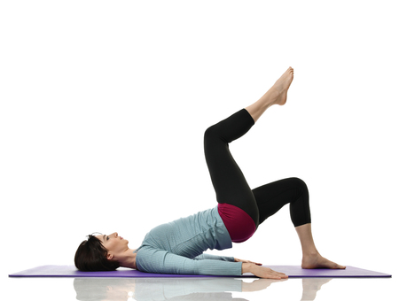 Foto de Mother woman exercising doing postnatal workout. Female fitness instructor holds legs in gym and workout exercises for abdominals with athletic muscle body over white background - Imagen libre de derechos