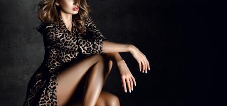 Foto de Beautiful sexy woman posing in Leopard print dress on dark  background - Imagen libre de derechos