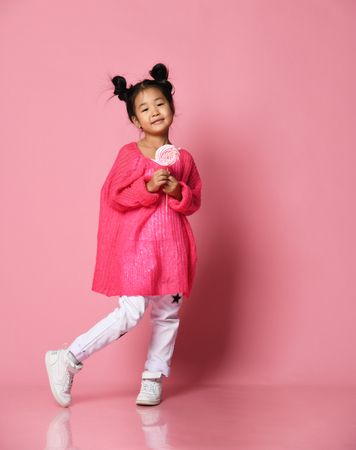 Photo for Happy young asian little girl kid lick eat happy big sweet lollypop candy on pink background - Royalty Free Image