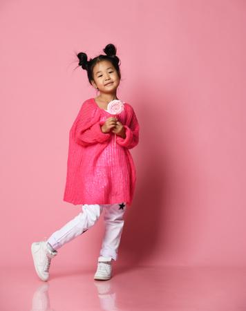 Foto de Happy young asian little girl kid lick eat happy big sweet lollypop candy on pink background - Imagen libre de derechos