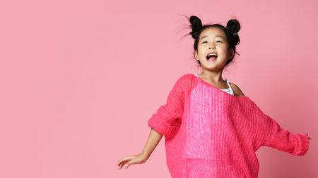 Photo pour Asian kid girl in pink sweater, white pants and funny buns sings happy smiling on pink background - image libre de droit