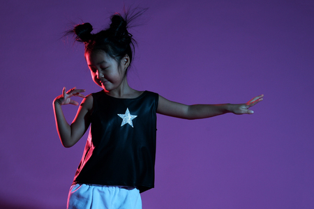 Photo pour Joyfull asian kid girl in shirt and pants with stars and on purple background dance - image libre de droit