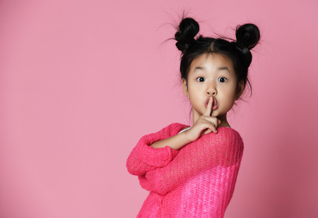 Foto de Asian kid girl in pink sweater shows shh sign on pink background. Close up portrait - Imagen libre de derechos