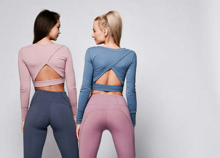 Photo pour Two sporty blonde and brunette girls in athletic body cloth sport wear cloth stand together after workout on gray background - image libre de droit