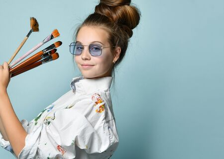 Photo pour Portrait in profile of happy smiling young woman with hair tied in a bun in white shirt with colorful paint stains holding a set of brushes on gray background with free copy space - image libre de droit