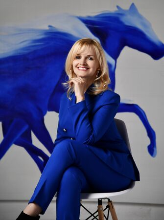 Foto de Young blonde businesswoman in stylish deep blue official costume sits on chair looking at us with flying blue paint art at background. Fashion and stylish office look concept - Imagen libre de derechos