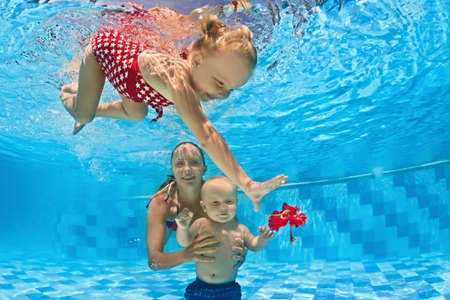 Foto de Young mother teaches to swim 10 month old baby - dive with cheerful child deep into the blue water, healthy lifestyle and children underwater swimming lessons with an instructor in the pool - Imagen libre de derechos