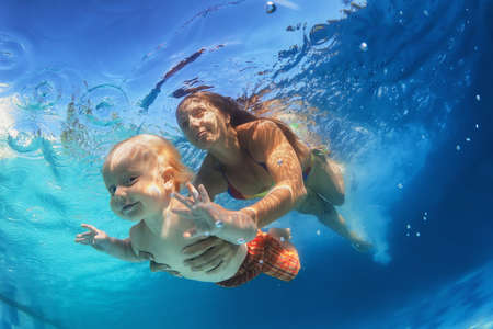 Photo pour In blue pool young mother swimming with happy baby son - dive underwater with cheerful boy. Healthy family lifestyle and children water sports activity with parents during summer vacation with child - image libre de droit