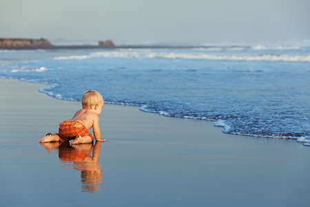Photo pour On the sunset beach funny baby crawling on black wet sand to sea surf for swimming in the waves. Family lifestyle and water activity during summer vacation with child on the tropical Bali island - image libre de droit