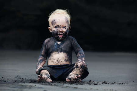 Photo pour Funny portrait of smiling child with dirty face sitting and playing with fun on black sand sea beach before swimming in ocean. Family active lifestyle and water leisure on summer vacation with baby - image libre de droit