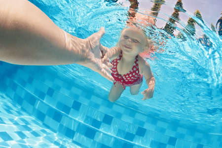 Foto de Joyful baby girl diving underwater with fun and holding parents hand for assistance in swimming pool. Healthy active family lifestyle, children water sport activity with mother on summer vacation - Imagen libre de derechos