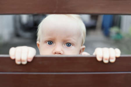 Photo for Portrait of abandoned by parents baby boy with staring blue eyes, sad and lonely face expression, looking out through fence. Social problems, family abuse, children stress and negative emotions - Royalty Free Image