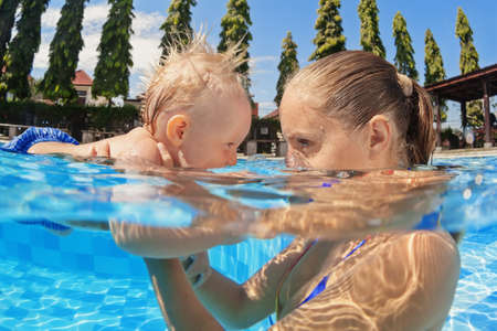 Photo pour Portrait of boy having fun in pool with joyful mother. Healthy family lifestyle, water sports activity, baby swimming and diving underwater lessons with active parents on summer holidays with children - image libre de droit