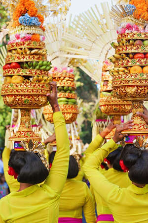 Photo for Procession of beautiful Balinese women in traditional costumes carry ritual offerings on heads for Hindu ceremony. Arts festival, culture of Bali people, and Indonesia islands. Asian travel background - Royalty Free Image