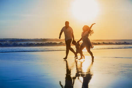 Foto de Happy family - father, mother, baby son hold hands and run with fun along edge of sunset sea on black sand beach. Active parents and people outdoor activity on tropical summer vacations with children - Imagen libre de derechos