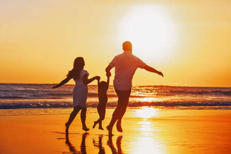 Photo pour Happy family - father, mother, baby son hold hands and run with fun along edge of sunset sea on black sand beach. Active parents and people outdoor activity on tropical summer vacations with children. - image libre de droit