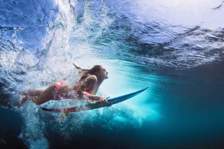 Foto de Young girl in bikini - surfer with surf board dive underwater with fun under big ocean wave. Family lifestyle, people water sport lessons and beach swimming activity on summer vacation with child - Imagen libre de derechos