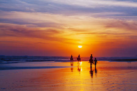 Foto de Black silhouette of happy family having horse riding adventure on sand sea beach on background of sunset sky. Active parents and people outdoor activity on tropical summer vacations with children. - Imagen libre de derechos